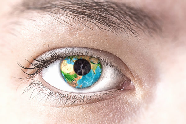 Close up of female eye with Earth planet. Elements of this image are furnished by NASA